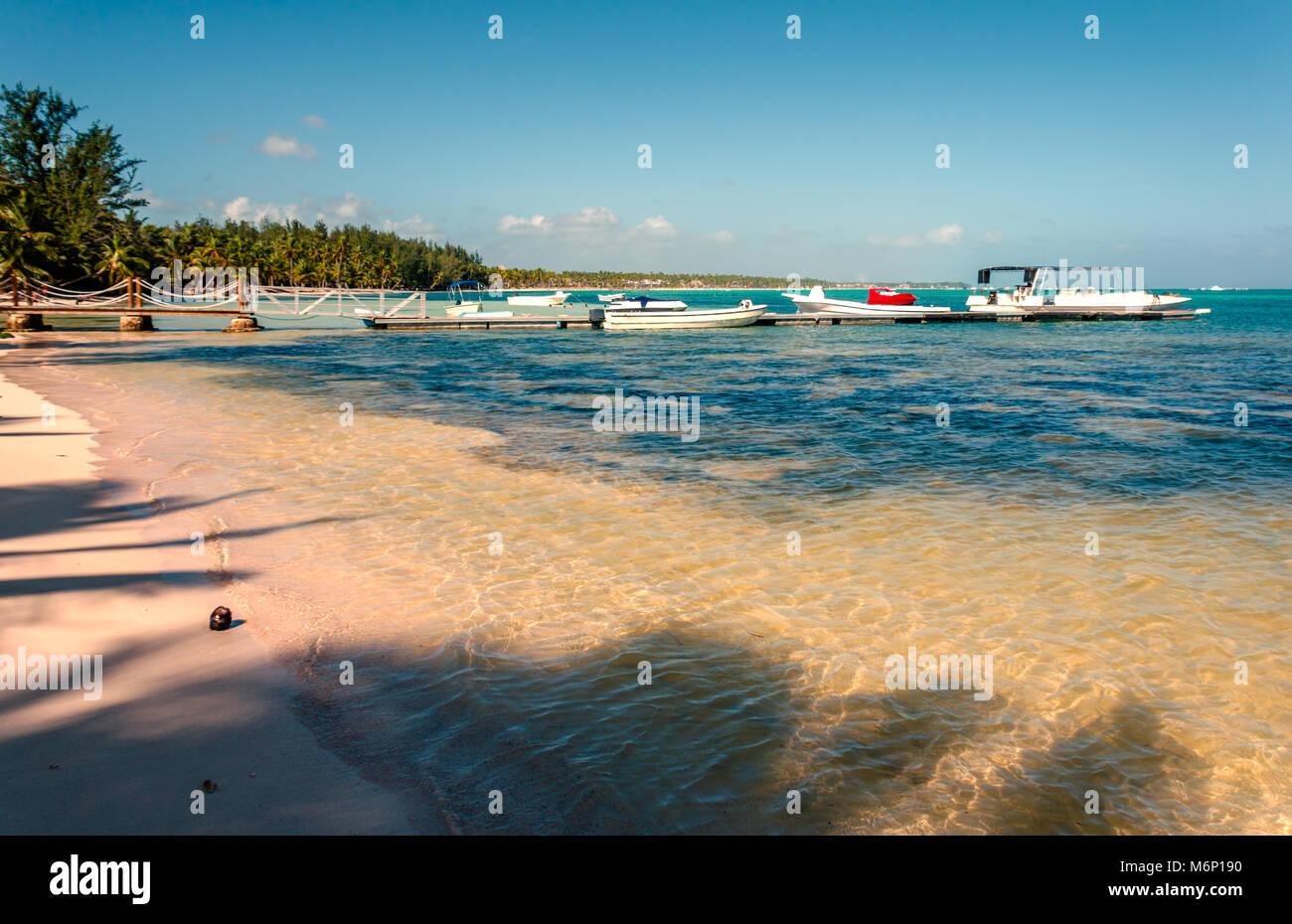 Una playa tropical con claras aguas del océano, coco en la perca, un embarcadero con botes y yates, palmerales Imagen De Stock