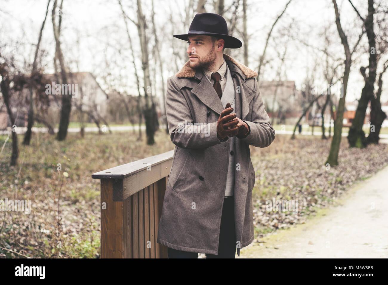 Apuesto hombre elegante en el parque llevar traje y abrigo. Imagen De Stock 9b45ce72448