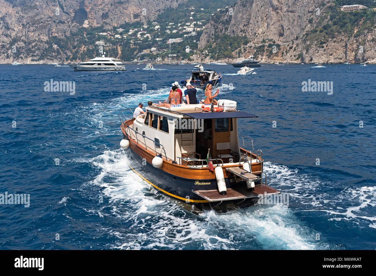 Los turistas en un viaje en barco alrededor de la isla de Capri, la bahía de Nápoles, Italia. Imagen De Stock