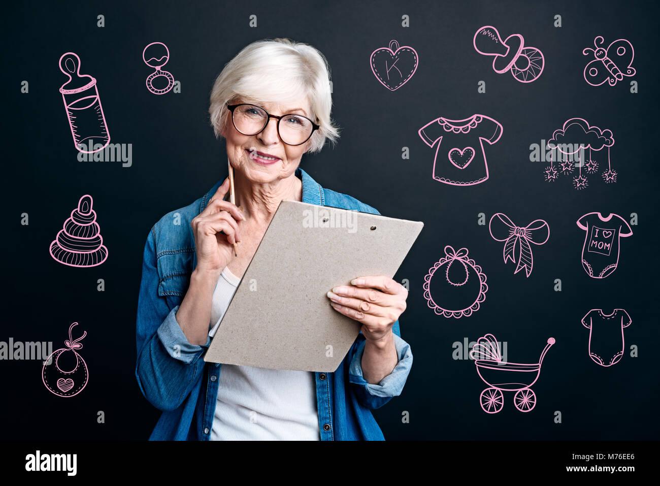 Abuela feliz haciendo una lista antes de ir a una fiesta de cumpleaños Foto de stock