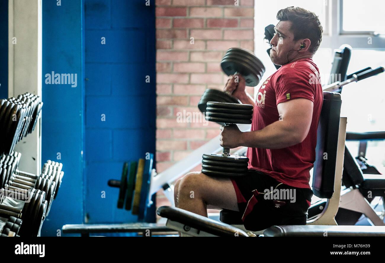 Hombre de trabajo muscular con pesas en el gimnasio. Imagen De Stock