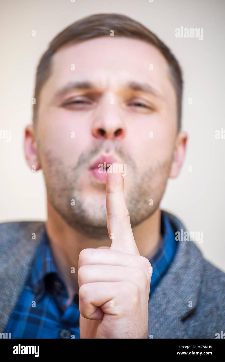 Retrato de etnia caucásica joven hombre apuntando con su dedo índice hacia arriba y soplando sobre ella Imagen De Stock