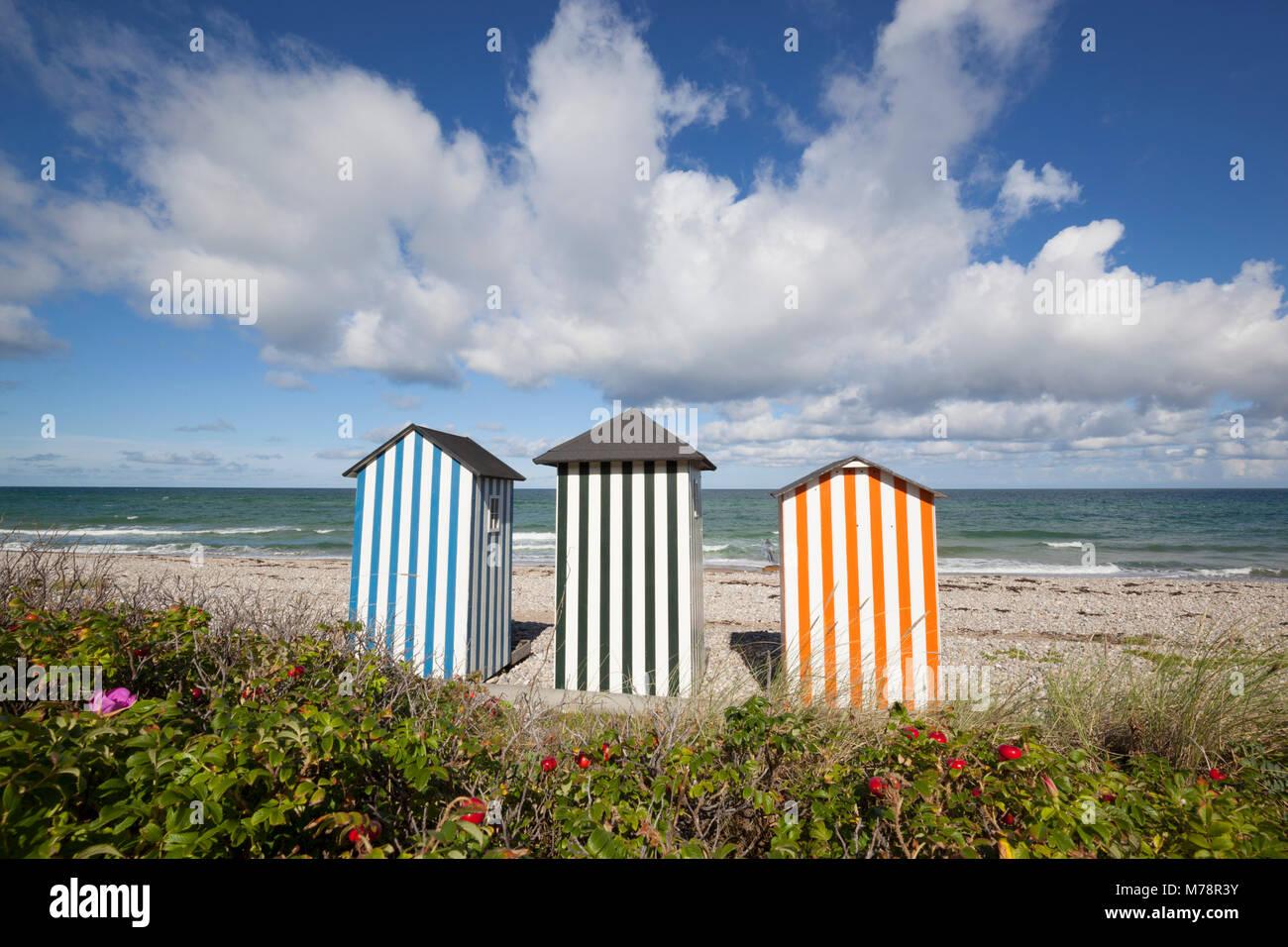Coloridas casetas de playa en la playa de guijarros con el azul del mar y el cielo con nubes, Rageleje, Kattegat Foto de stock