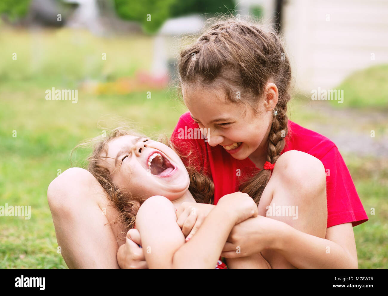 Dos niñas feliz abrazando y riendo en el parque Imagen De Stock