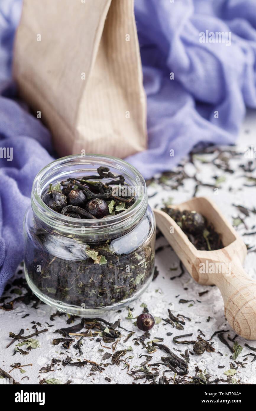 Té de hierbas saludables con grosellas negras en un frasco de vidrio y boca de madera. Vitamina bebida. Dieta. Imagen De Stock
