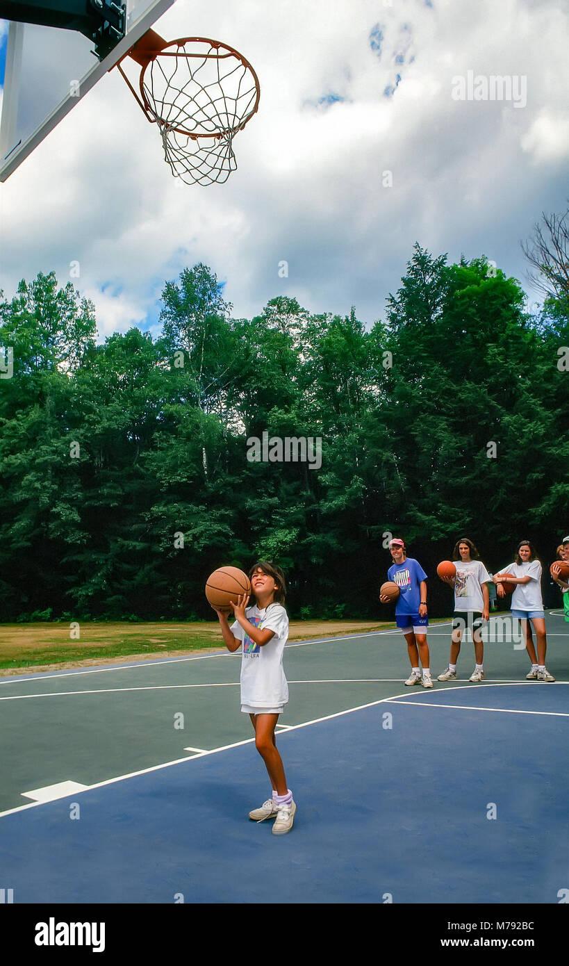 Una joven intenta disparar un aro de baloncesto en el campamento de verano en Vermont, Estados Unidos, América Imagen De Stock