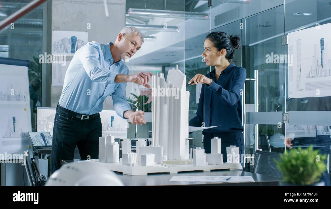 Dos profesionales masculinos y femeninos ingenieros trabajan con planos arquitectónicos y de construcción de un Foto de stock