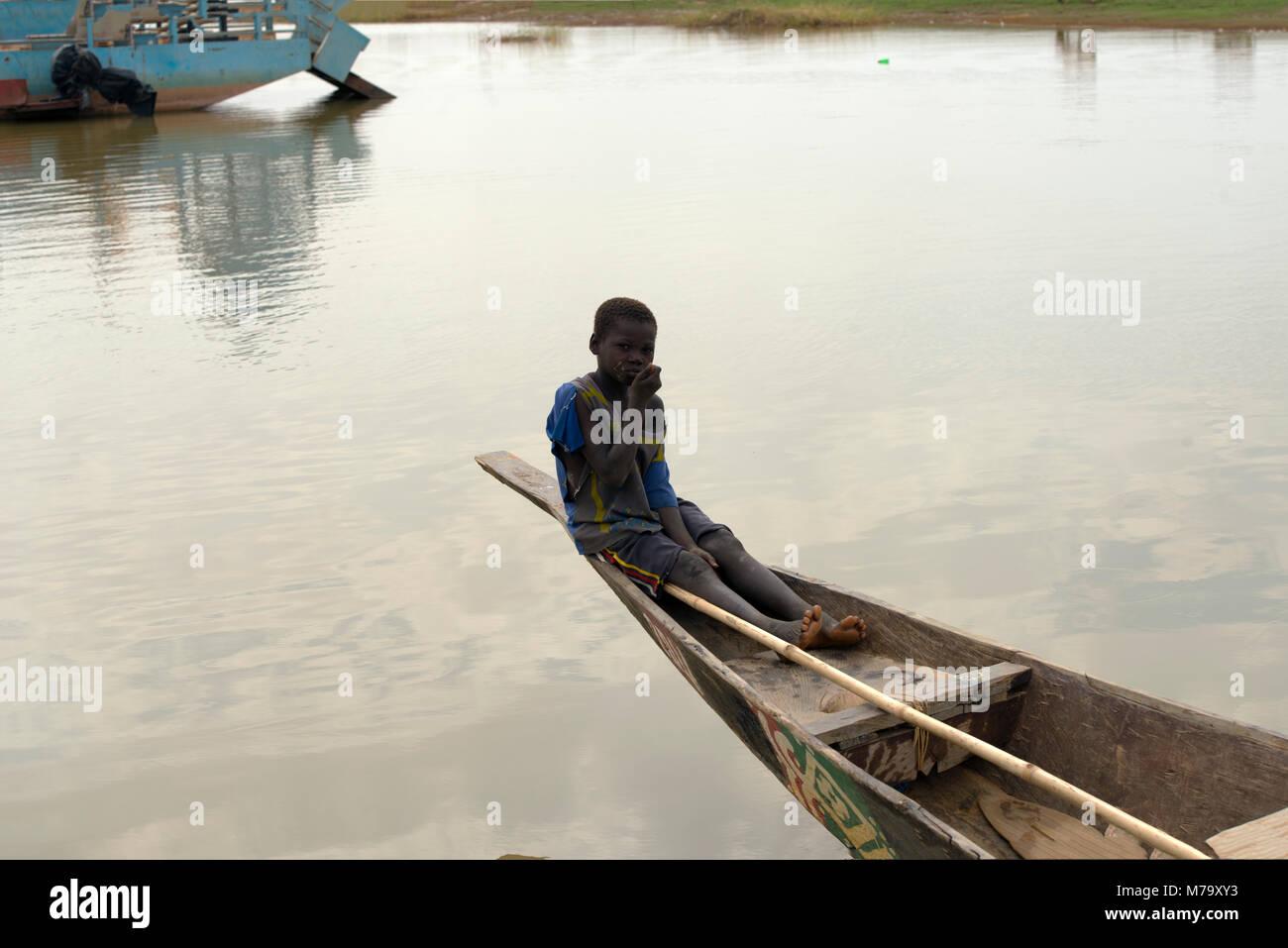 Un joven local muchacho sentado en la popa de una piragua (embarcación tradicional) en el río Bani. Región de Mopti, Foto de stock