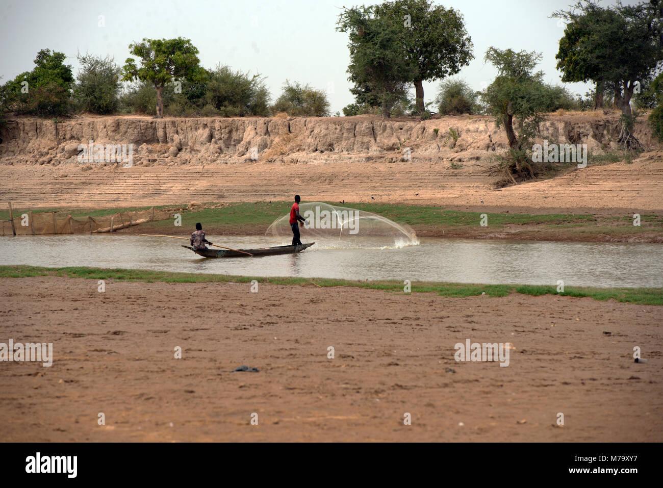 Un pescador arroja su red desde dentro de un barco. Región de Mopti, Malí, África occidental. Foto de stock