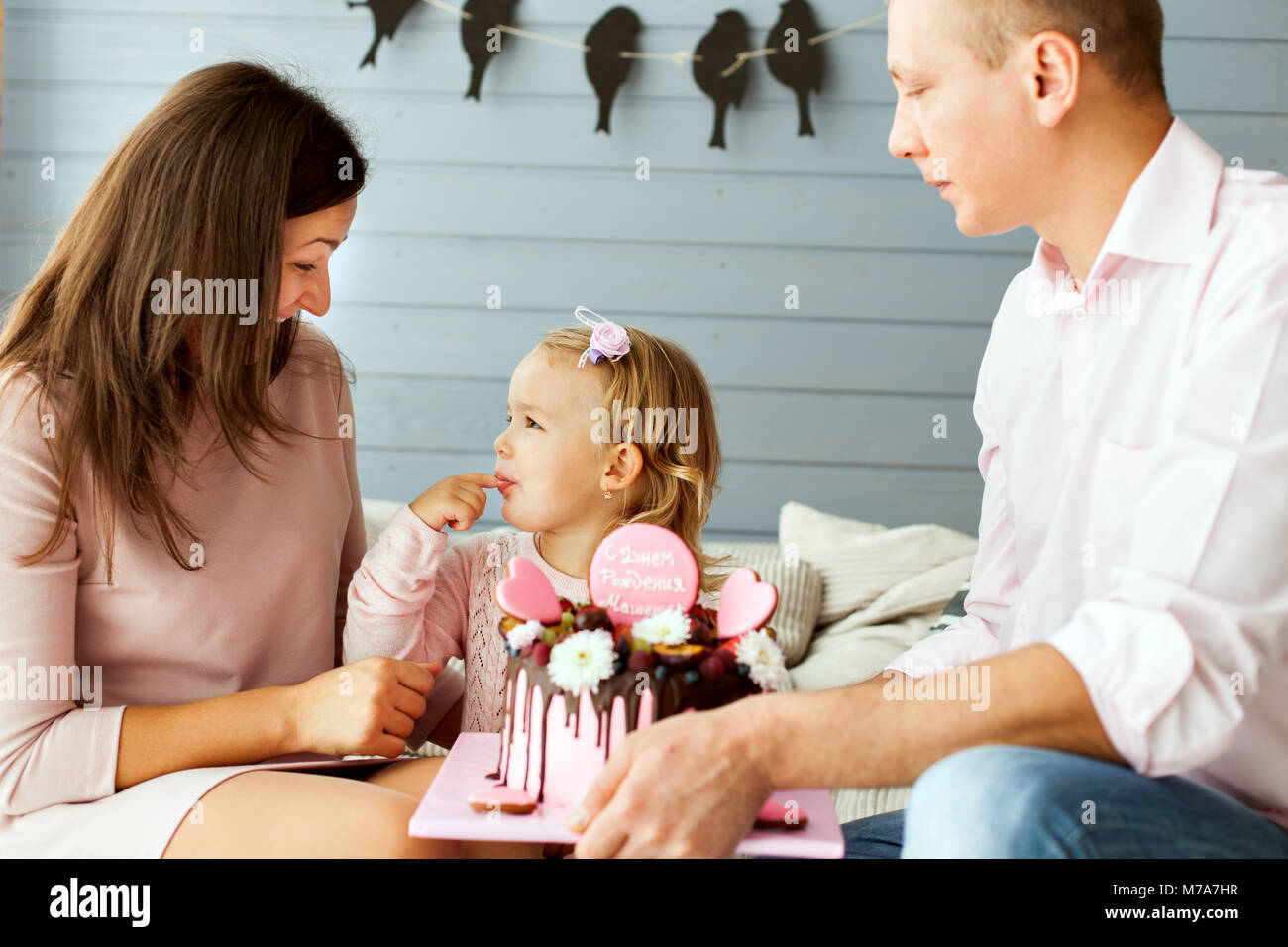 Los padres con un poco de hermosa hija. Chica está tratando el pastel con su dedo Imagen De Stock