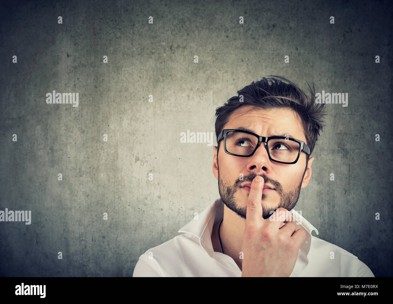 Joven apuesto hombre de gafas pensando en dudas y tocar los labios en gris. Foto de stock