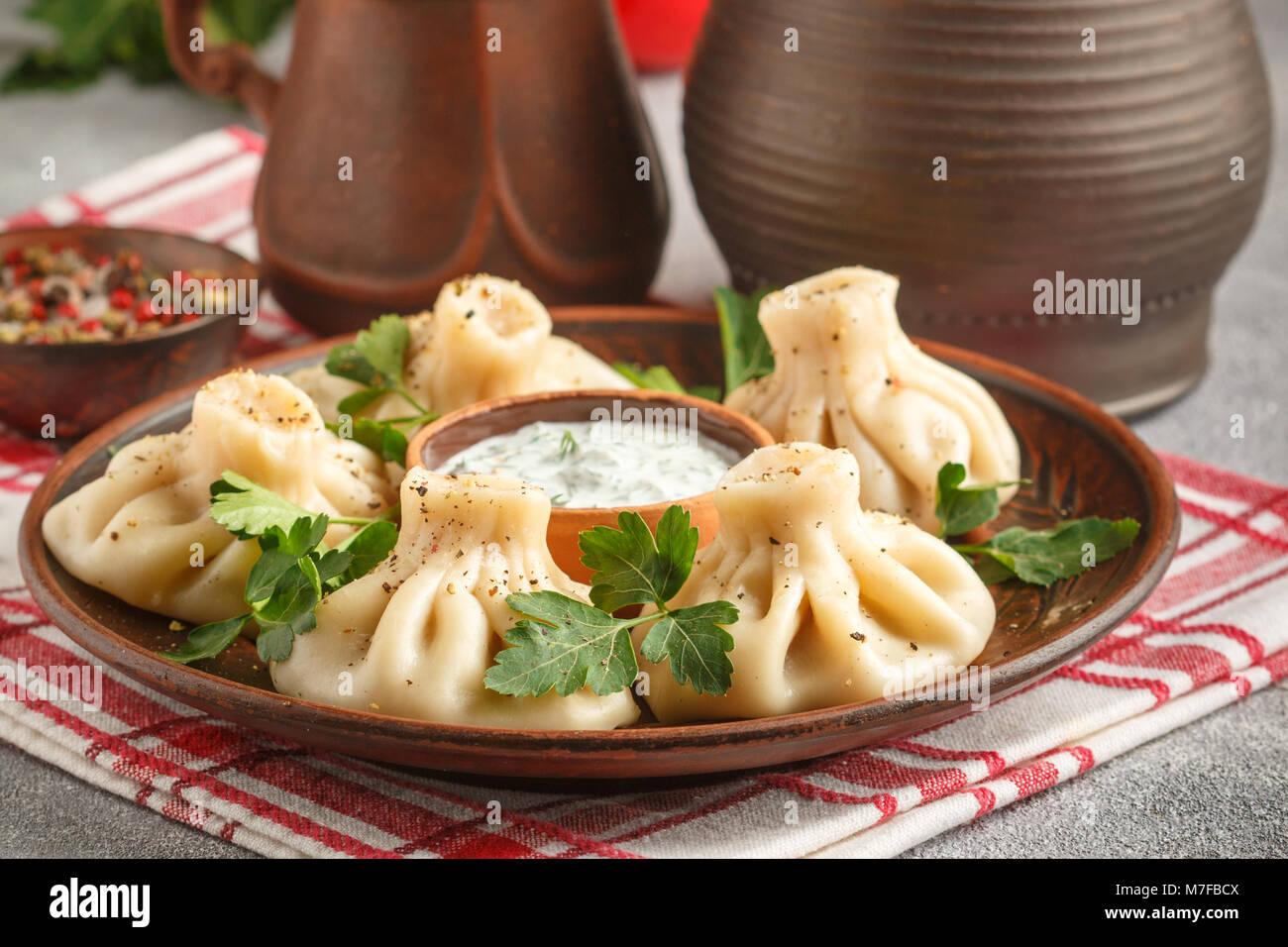 - El Georgian Khinkali dumplings con la carne y el perejil en un plato de cerámica con una salsa de crema agria Imagen De Stock