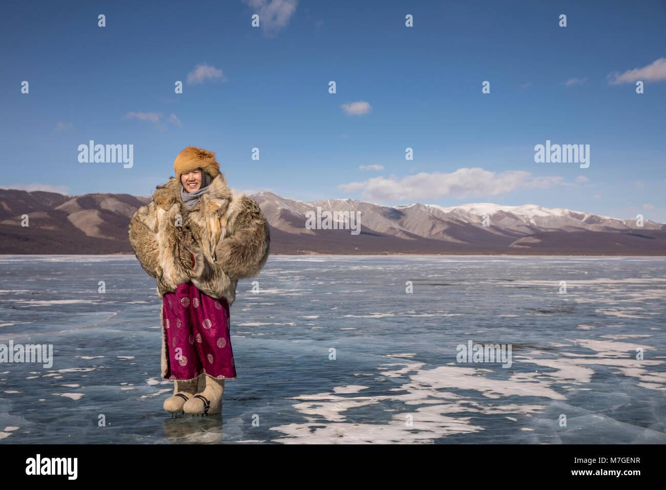 Joven dama mongola en wolfskin chaqueta en un lago congelado Khovsgol en el norte de Mongolia Imagen De Stock