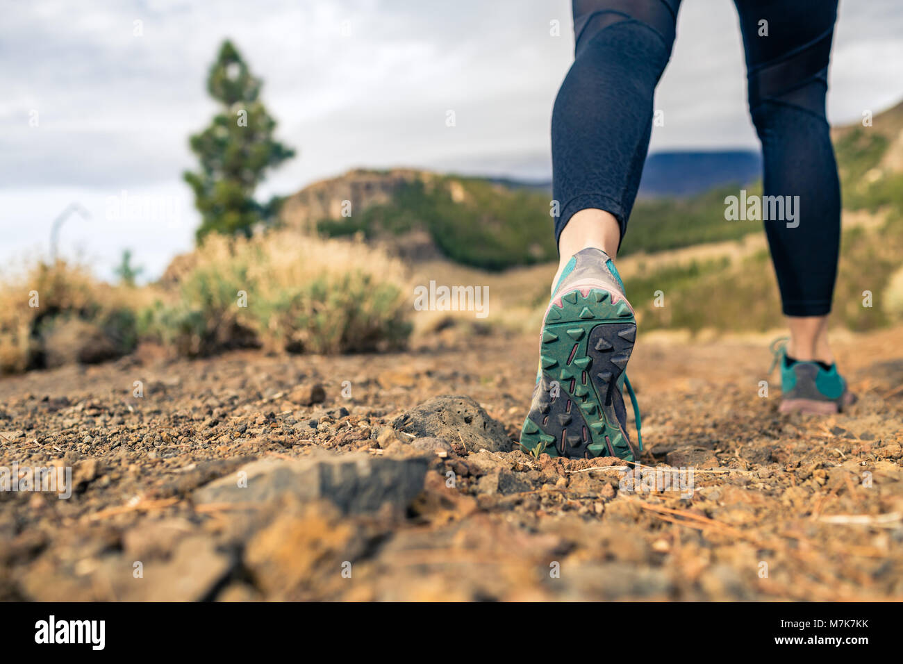 Suela de zapato deportivo caminando en las montañas en el camino rocoso. Corredor de cross country formación Imagen De Stock