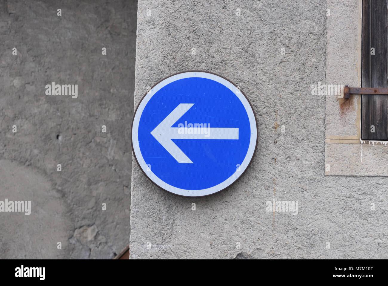 Azul y blanco Dirección de tráfico firmar en la forma de una flecha en un muro de piedra. Samoens, Haute Imagen De Stock