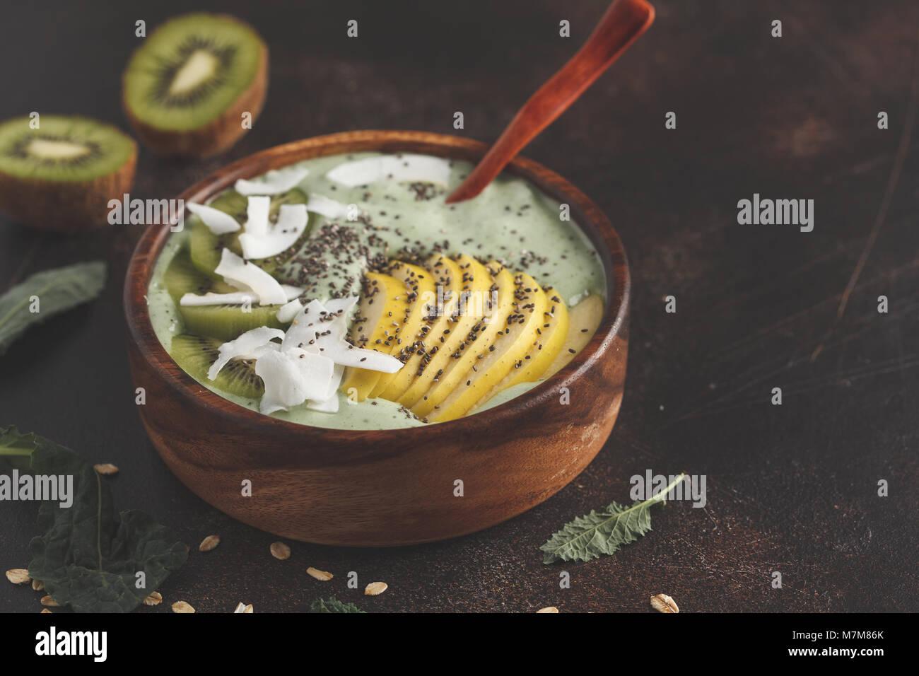 La col rizada verde batido vegano bowl con coco, chia, manzana y kiwi. Concepto de comida vegana saludable. Oxidado Imagen De Stock