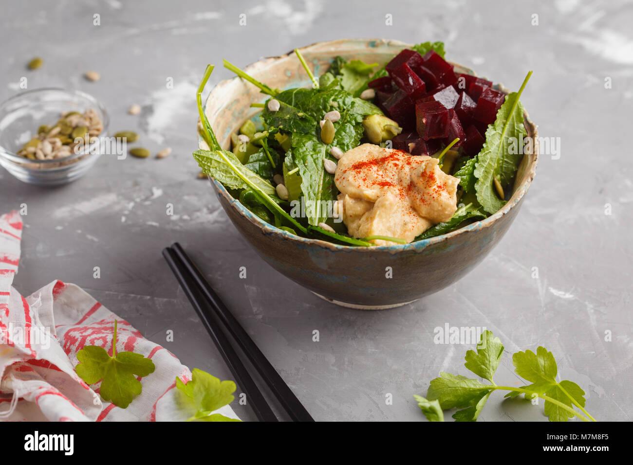 Vegan verde con ensalada de col, remolacha, pepino, semillas de girasol, con hummus vestirse. Concepto de comida Imagen De Stock
