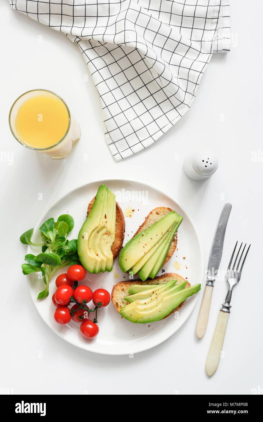 Las tostadas de aguacate y jugo de naranja sobre fondo blanco, vista superior. Concepto de desayuno saludable, un Imagen De Stock