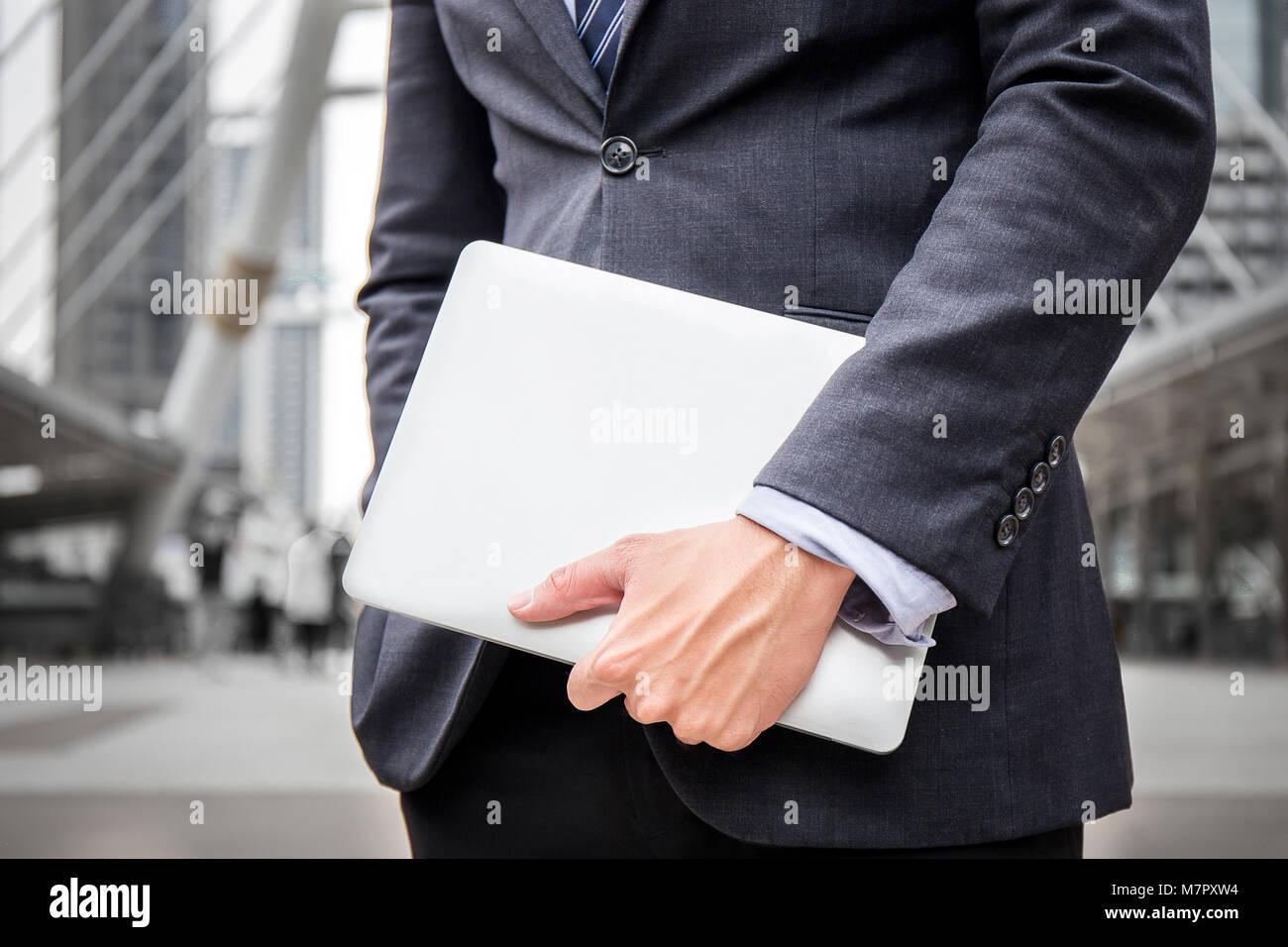 El empresario inteligente llevar traje mantenga portátil, equipo de oficina para su trabajo en el centro de Imagen De Stock
