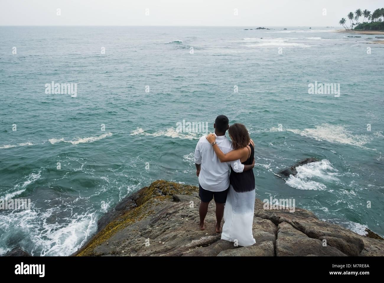 Sólo en una pareja casada trstone abrazos y miradas sobre el agua del océano Imagen De Stock