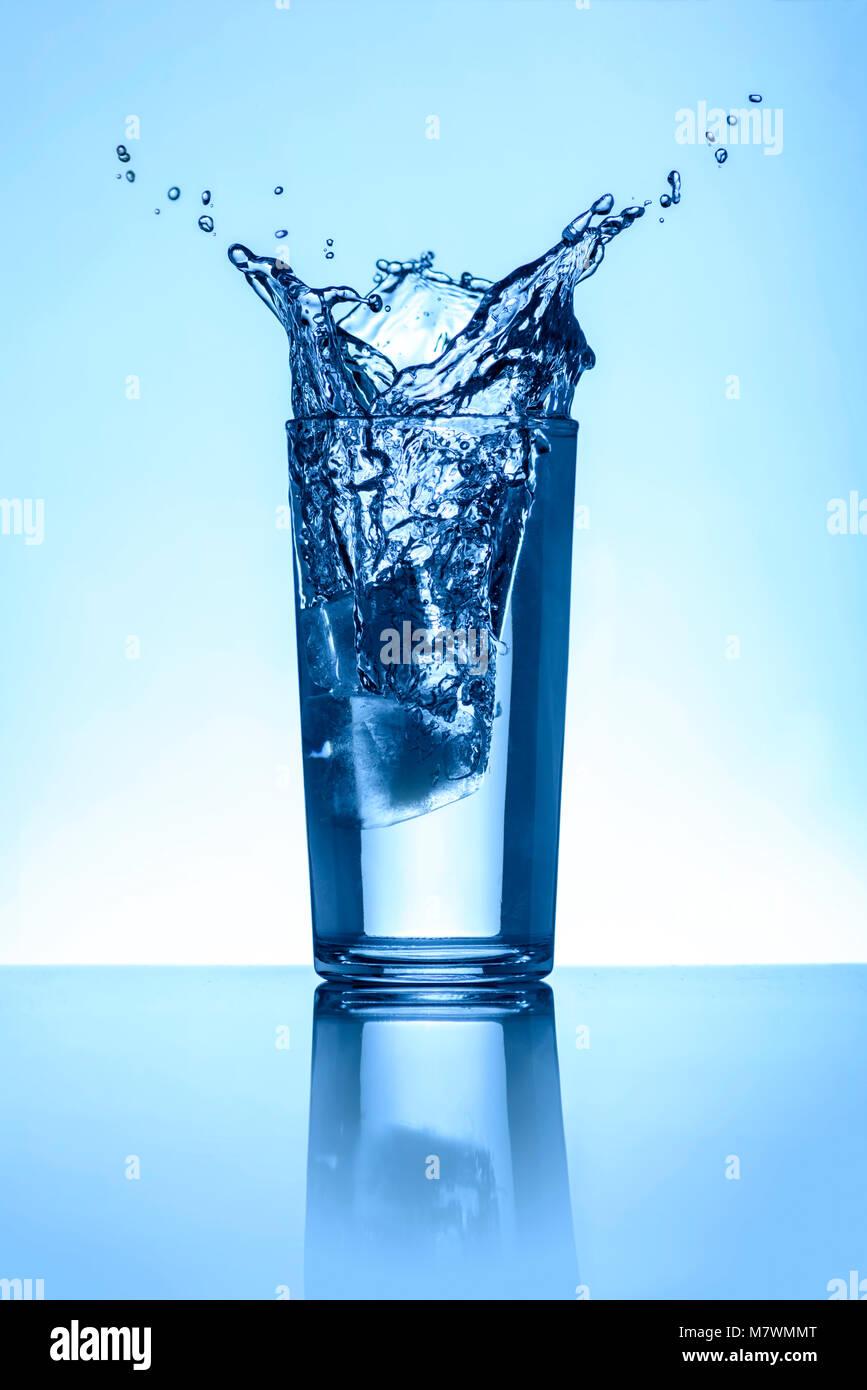Salpicaduras de agua natural en una Copa sobre fondo azul claro Foto de stock
