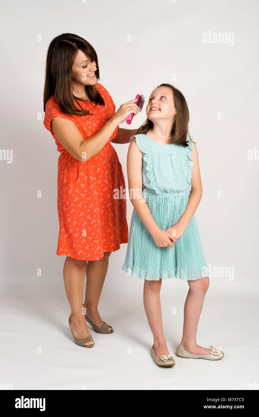 Cepillar el pelo de la madre de sus hijas. Imagen De Stock