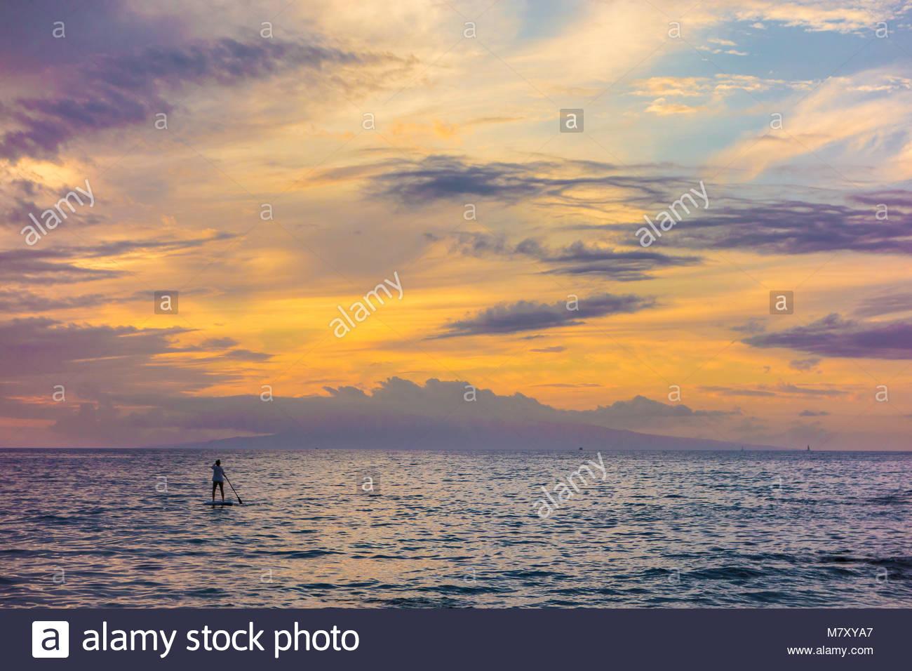 Paddleboarding y atardecer tropical de Kamaole Beach Park 3 del Océano Pacífico, en la isla de Maui en el estado de Hawaii, EE.UU. Foto de stock