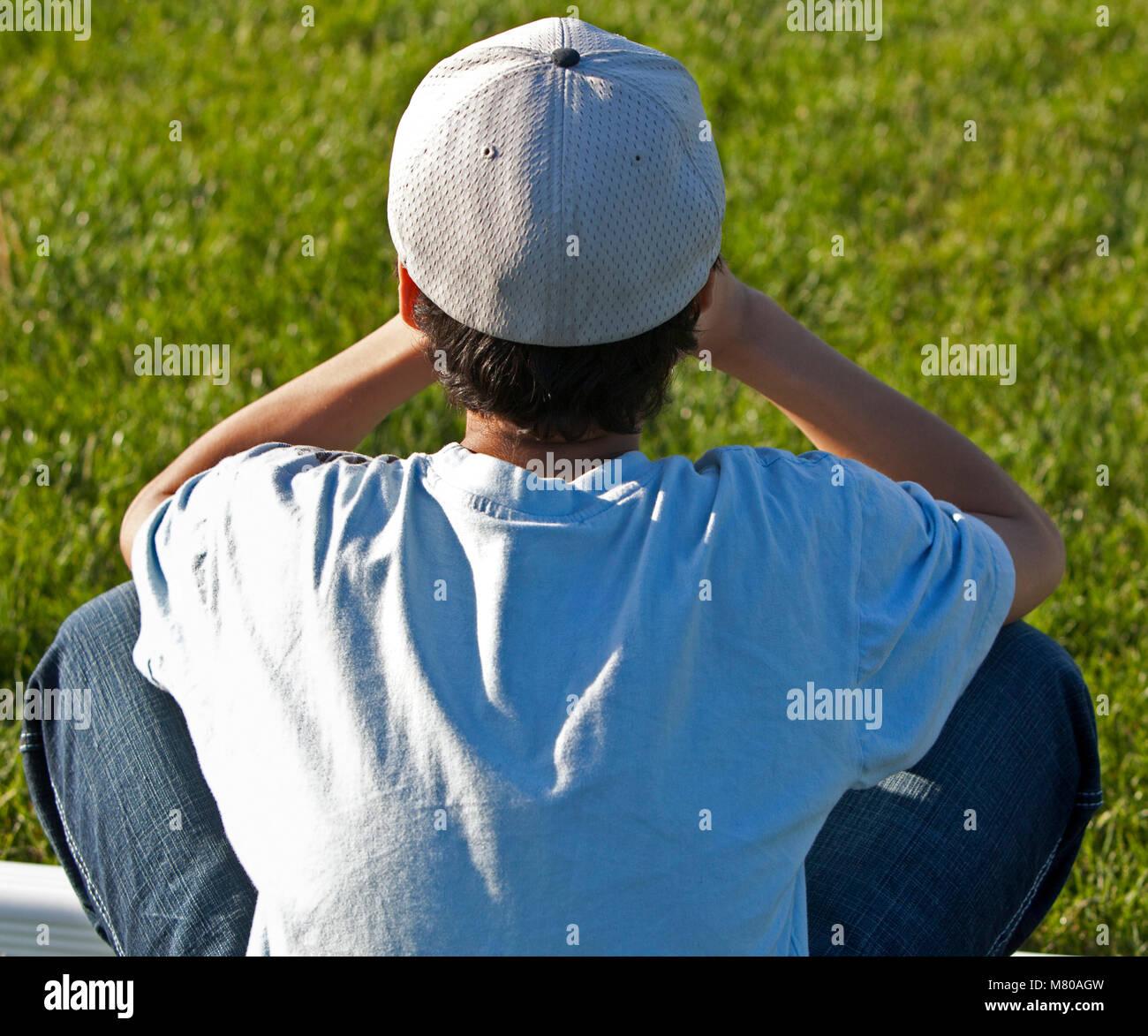 Muchacho sentado solo en el césped molesto y triste Imagen De Stock