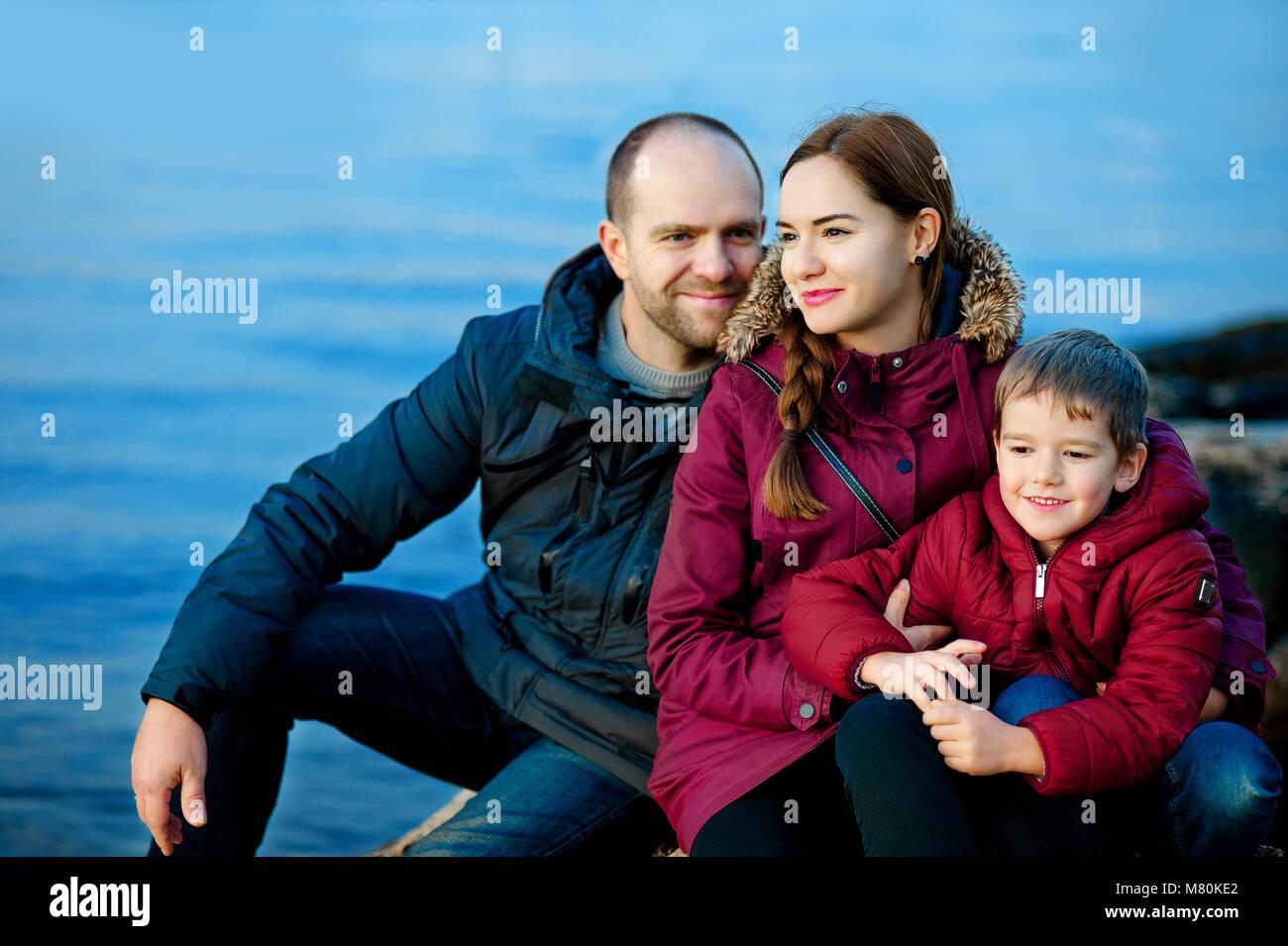 Familia mamá, papá e hijo sentado en la playa por el mar. Temporada: primavera, otoño. El concepto Imagen De Stock