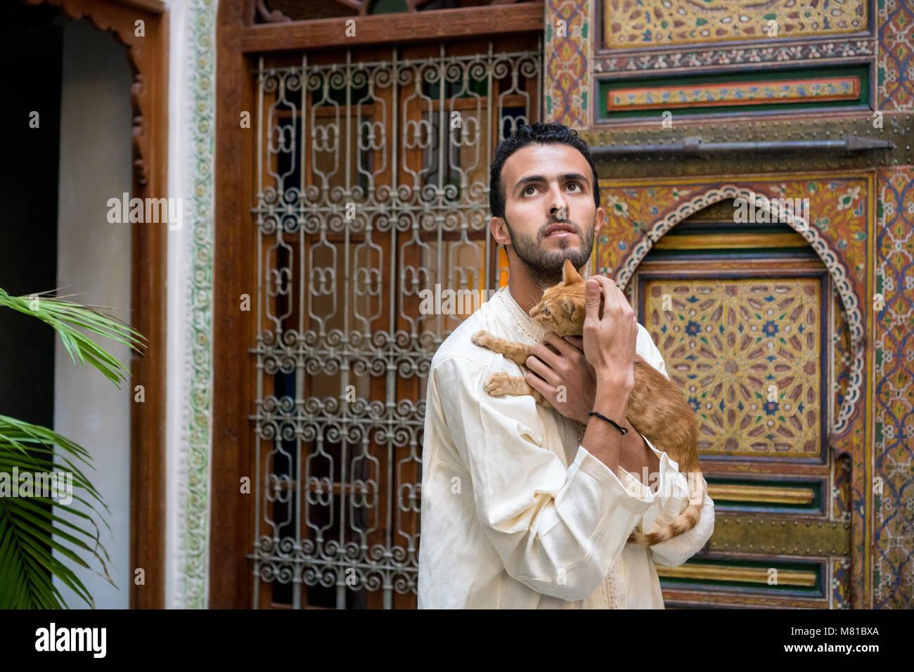 Joven musulmلn en vestimentas tradicionales sosteniendo un gato amarillo en el ambiente tradicional marroquí delante Foto de stock