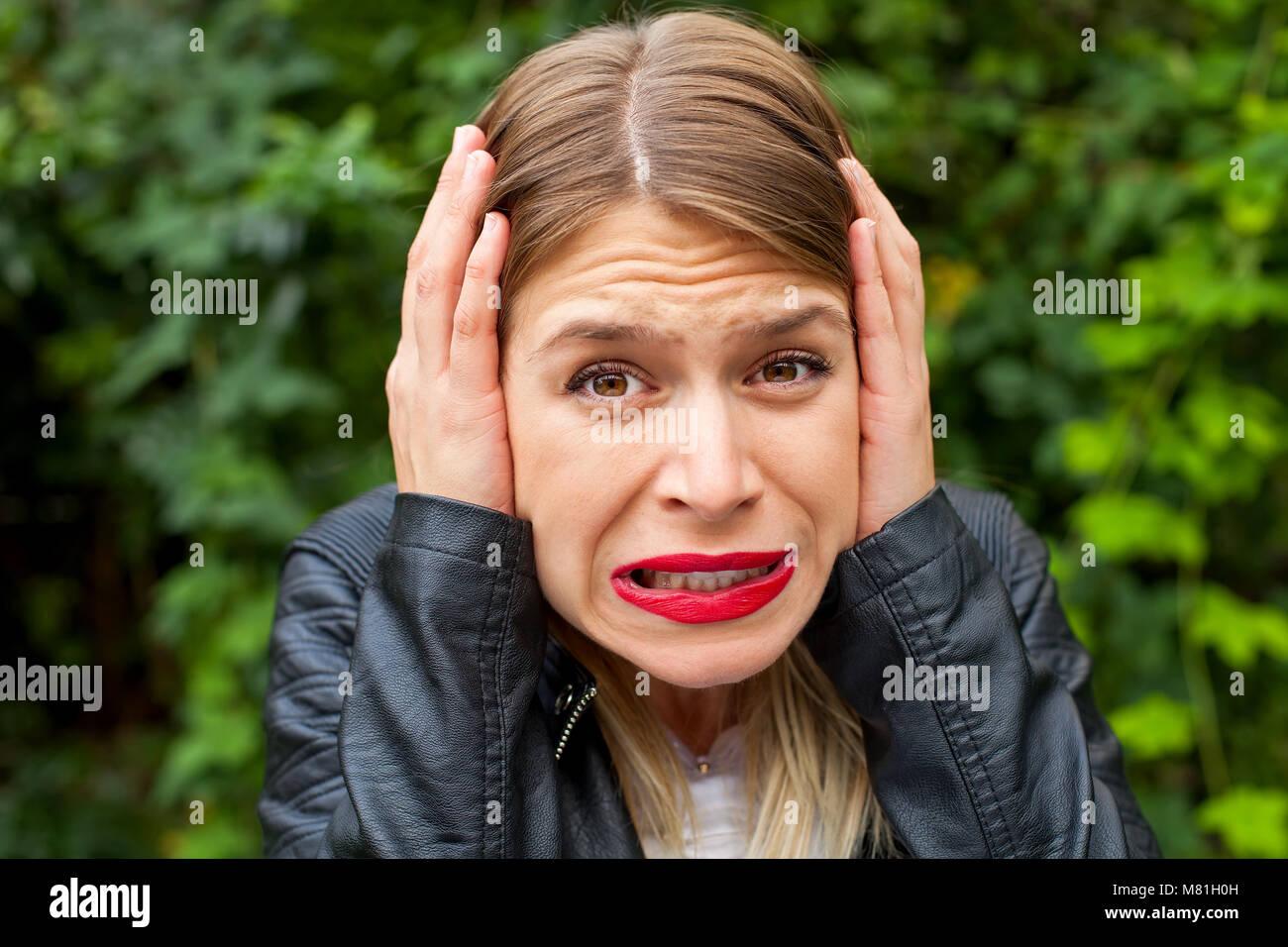 Mujer joven haciendo una mueca exterior, fondo verde. Triste - expresión malhumorada Imagen De Stock