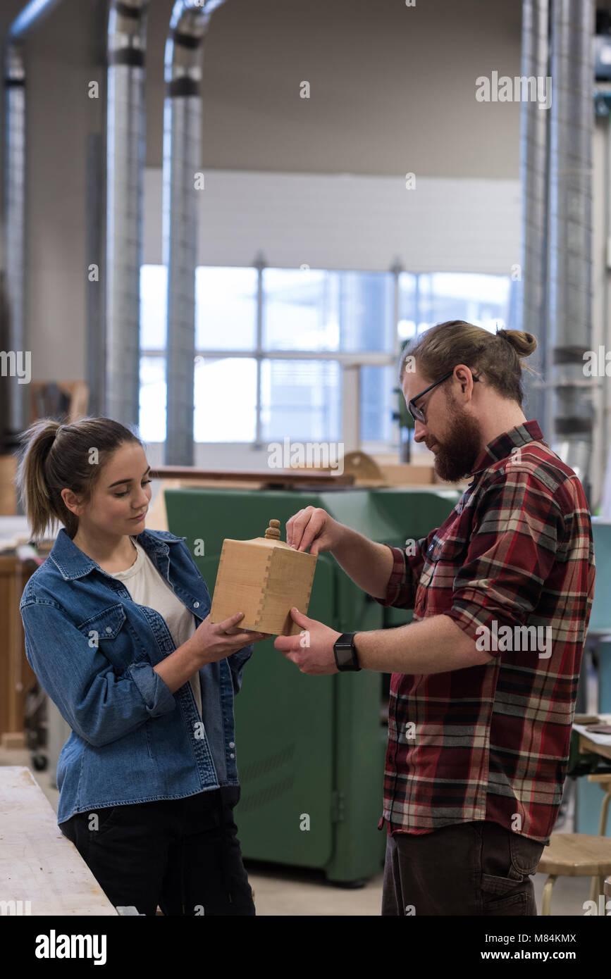 Macho y hembra carpinteros examinando un pedazo de muebles de madera Imagen De Stock