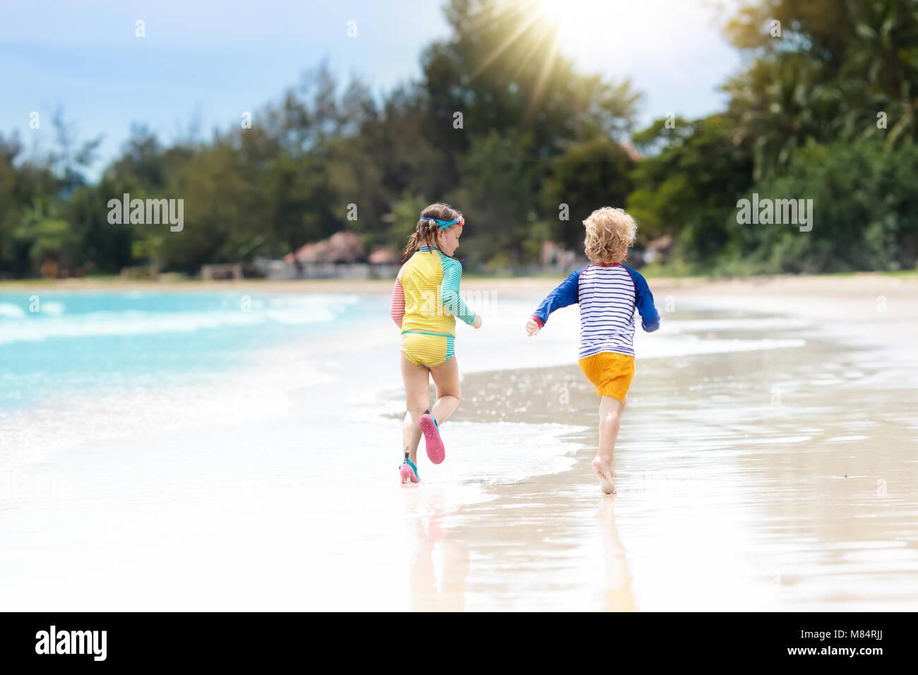 Niños Jugando En La Playa Tropical. Niña Excavando La