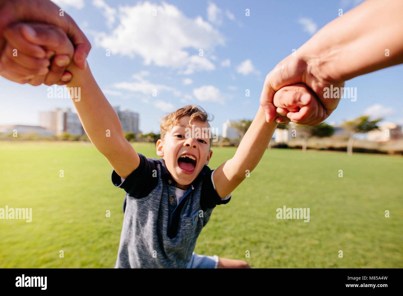 Niño alegre goza de ser levantado en el aire mientras jugaba en un parque. Cerca de un muchacho de buen humor Imagen De Stock