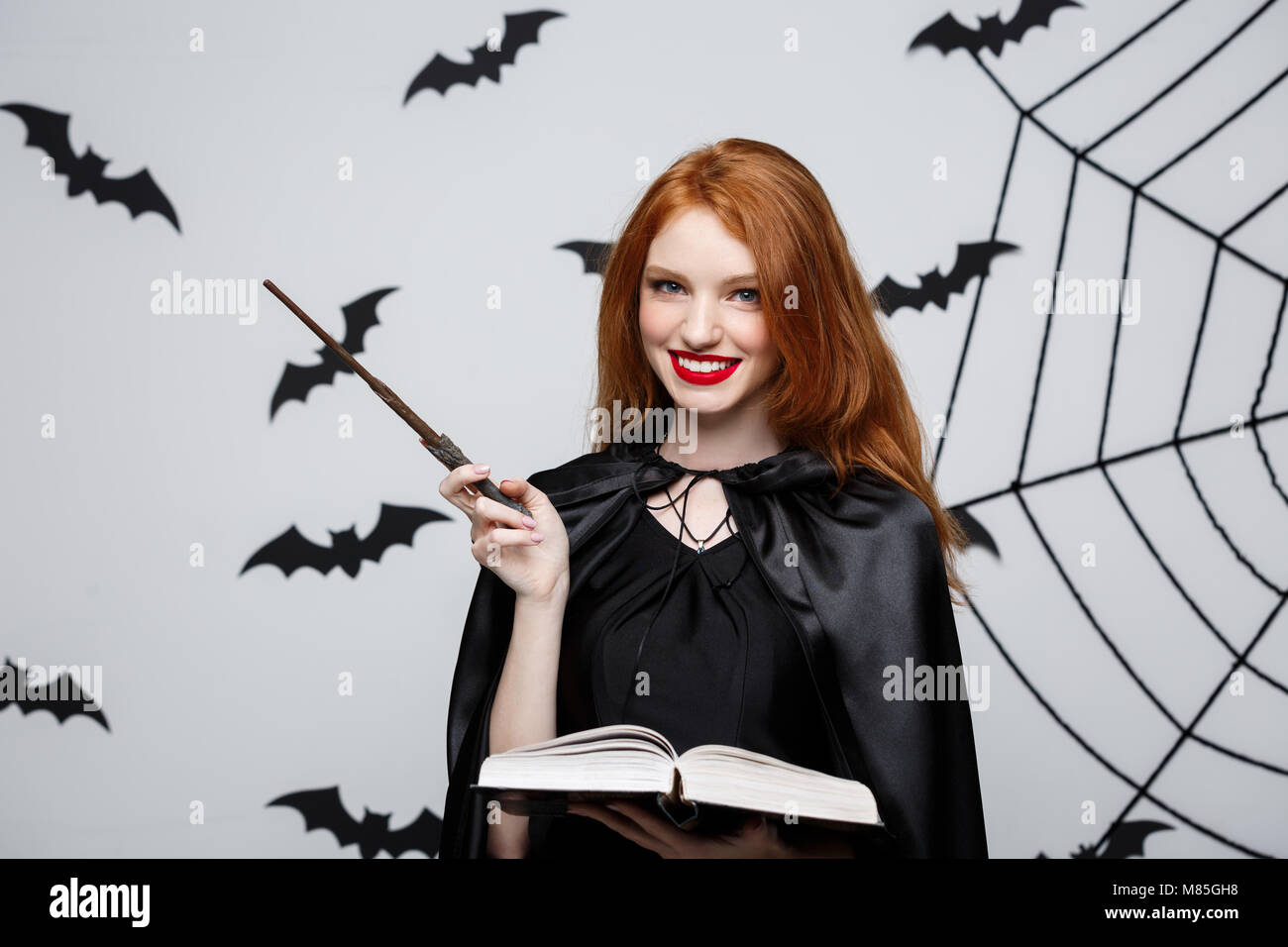 Concepto de Halloween - Hermosa Bruja jugando con la varita mágica y la magia del libro sobre fondo gris. Foto de stock
