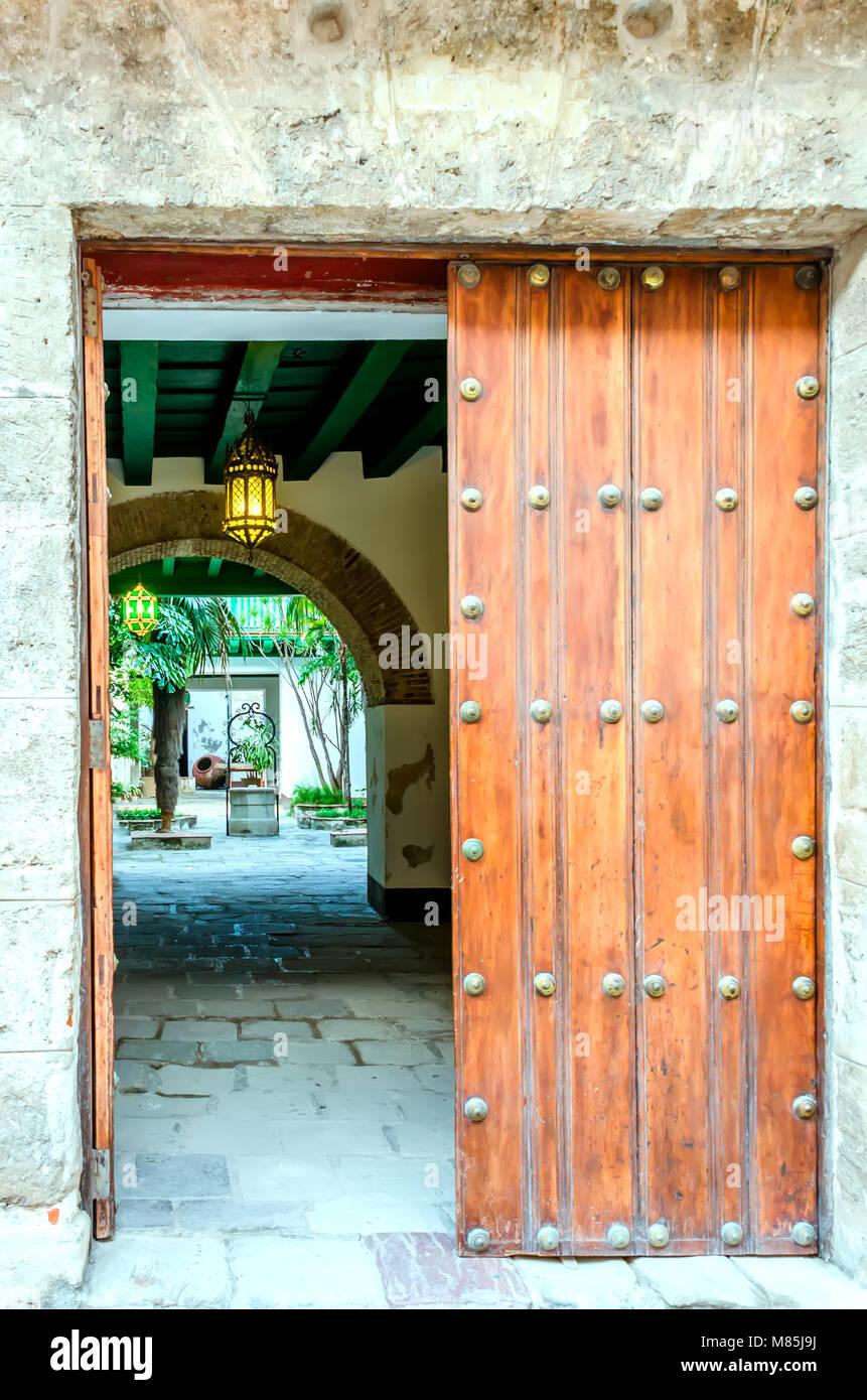 La antigua puerta de madera en una pared de piedra gris, en un patio con un arco luminoso, farolas, palmeras, un Imagen De Stock