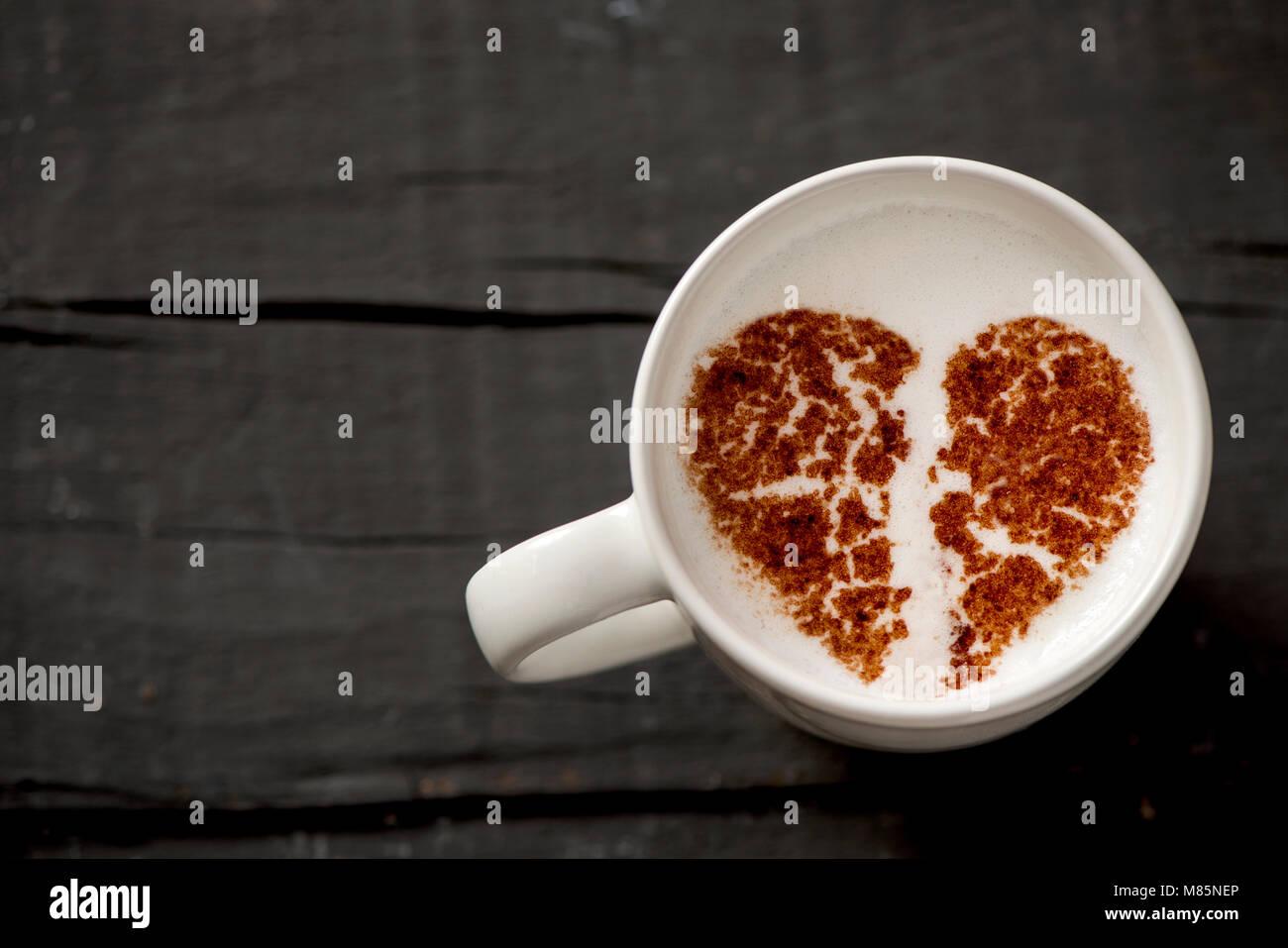 Disparo de alto ángulo de cerámica blanca taza de cappuccino con un corazón roto dibujado con cacao Imagen De Stock