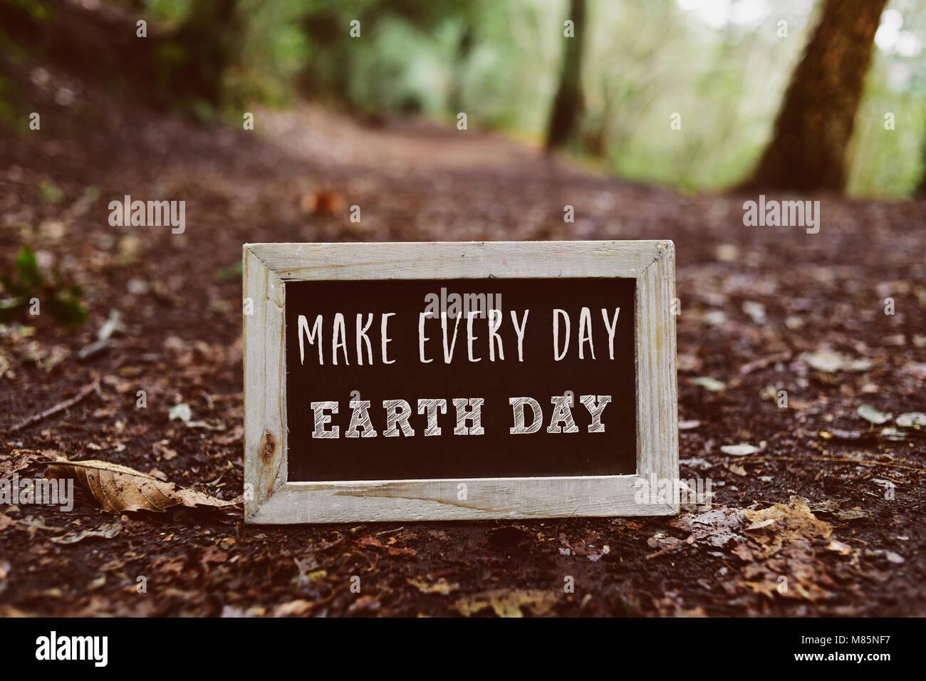 Primer plano de una pizarra con armazón de madera con el texto hacen cada día el día de la tierra Imagen De Stock