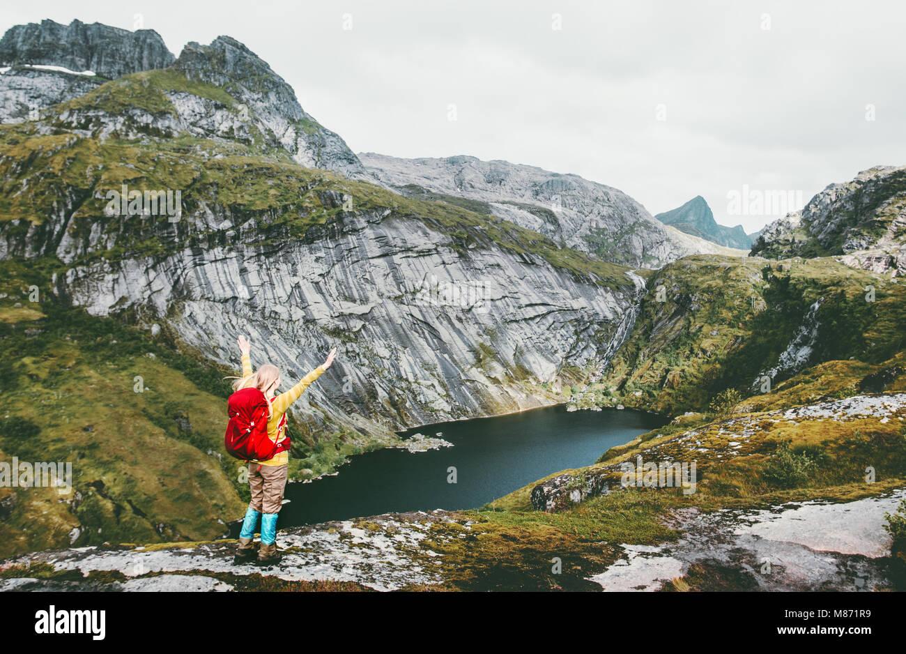 Mujer alegre y manos levantadas con mochila de senderismo en el lago en las montañas de Noruega Viajes de aventura Imagen De Stock