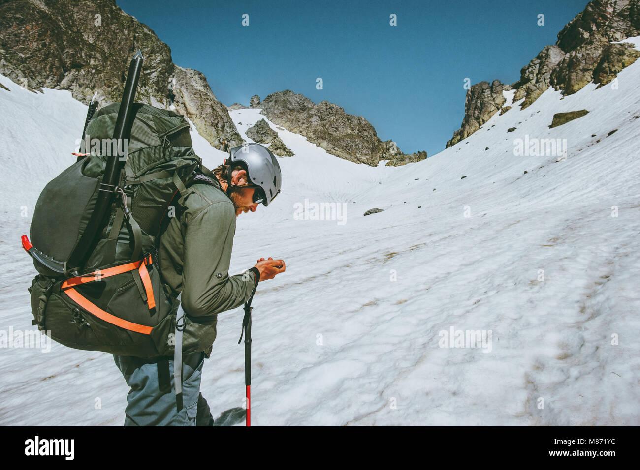Hombre aventurero con Tracker GPS Navigator comprobando las coordenadas de ubicación la escalada en las montañas Imagen De Stock