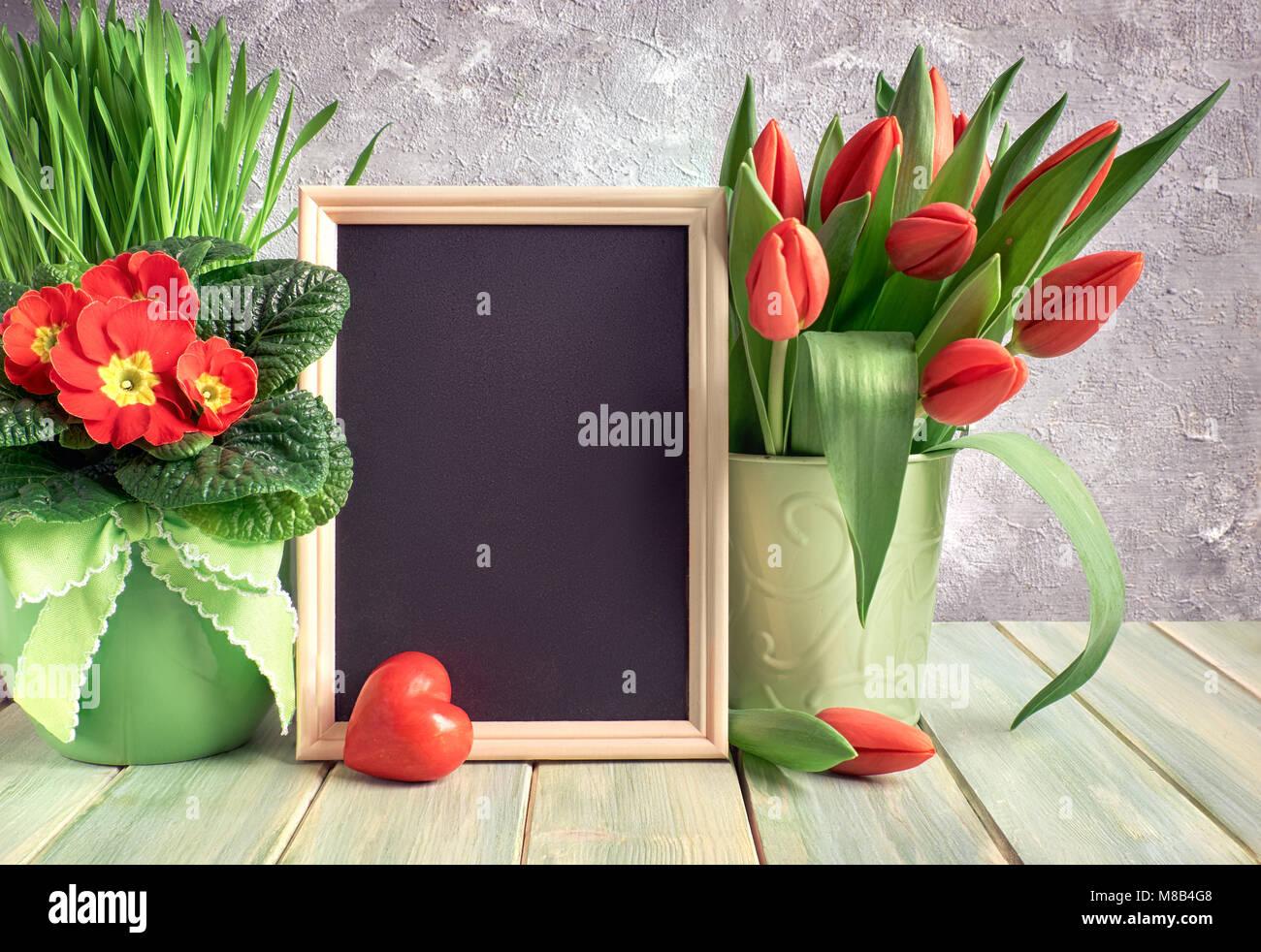 Composición de Pascua con corazón de piedra roja y rojo flores de ...