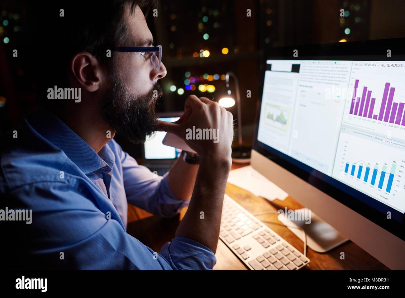 Joven empresario mirando su equipo en la oficina por la noche Foto de stock