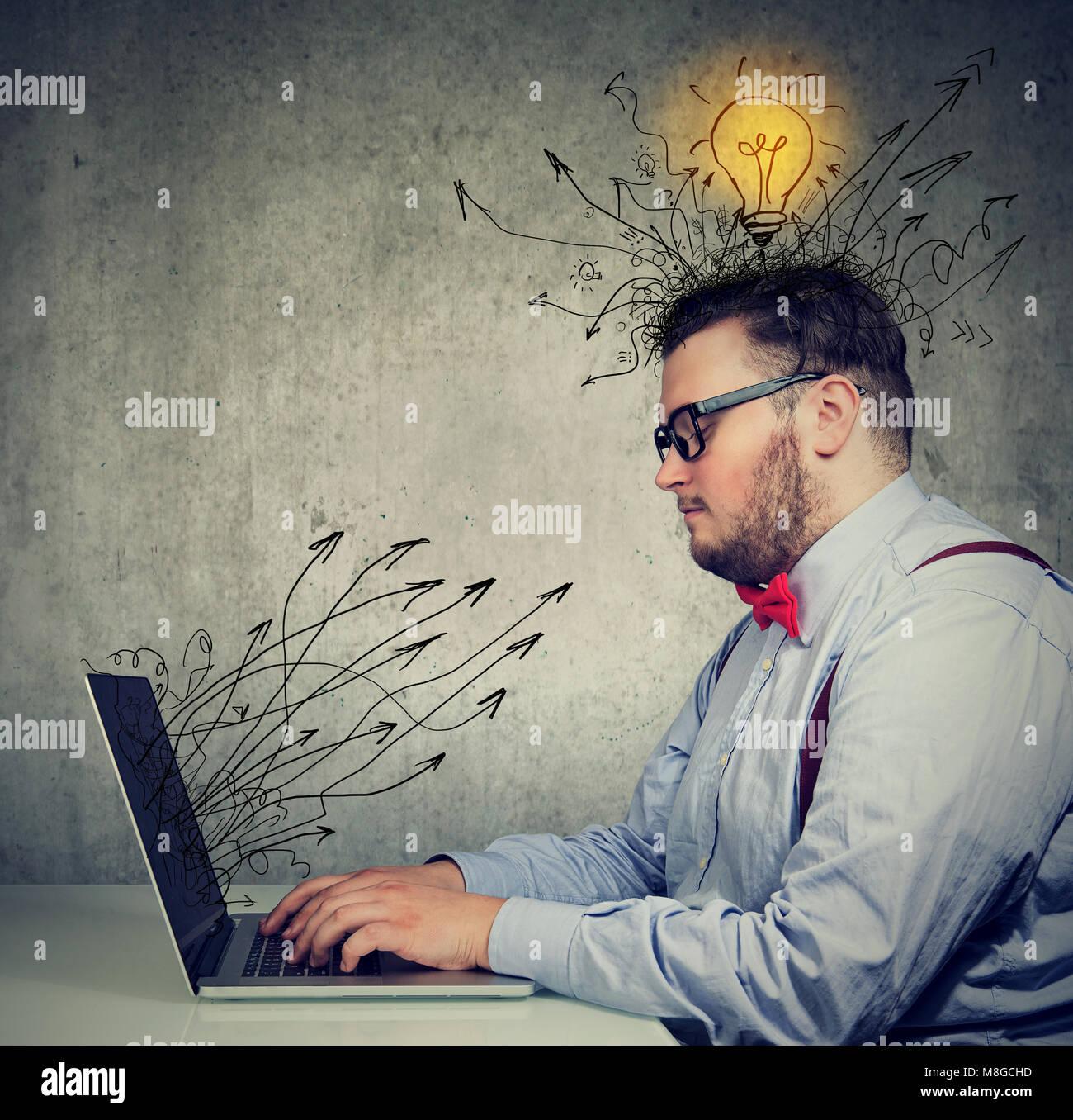 El hombre de negocios joven trabajando en el portátil tiene ideas brillantes Imagen De Stock