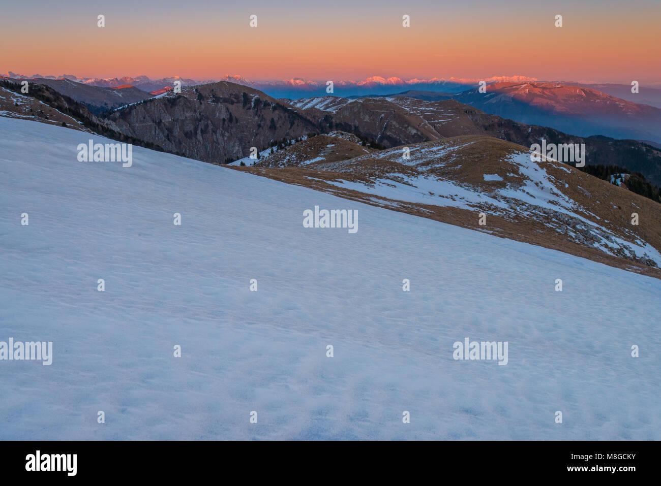 Pinturas alpenglow majestuosas montañas y nubes al atardecer, mirando hacia el valle. La nieve fresca convierte las cimas y laderas de color blanco, la primera nieve del invierno. Foto de stock