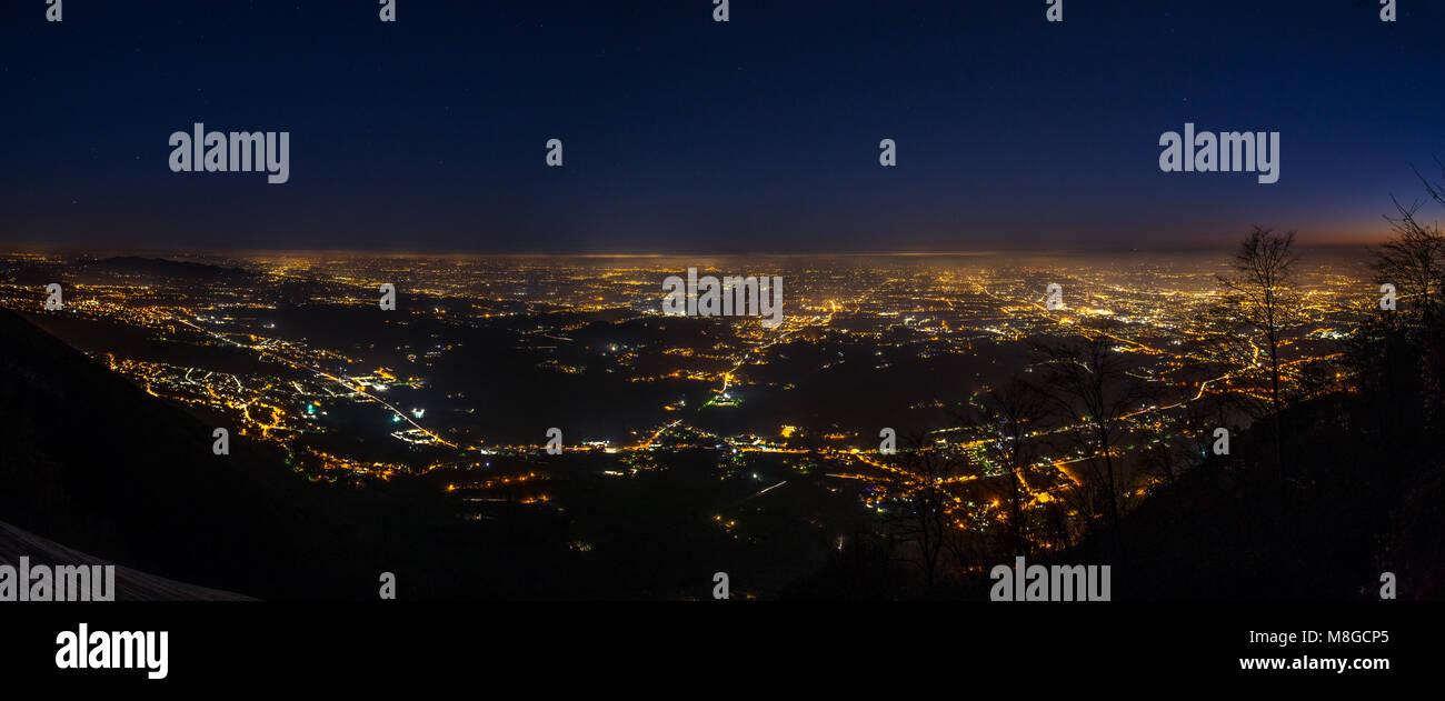 Las luces de la ciudad desde la cima del Monte Grappa. La contaminación lumínica que sale de ciudades y pueblos de los llanos. Fotografía nocturna. Foto de stock