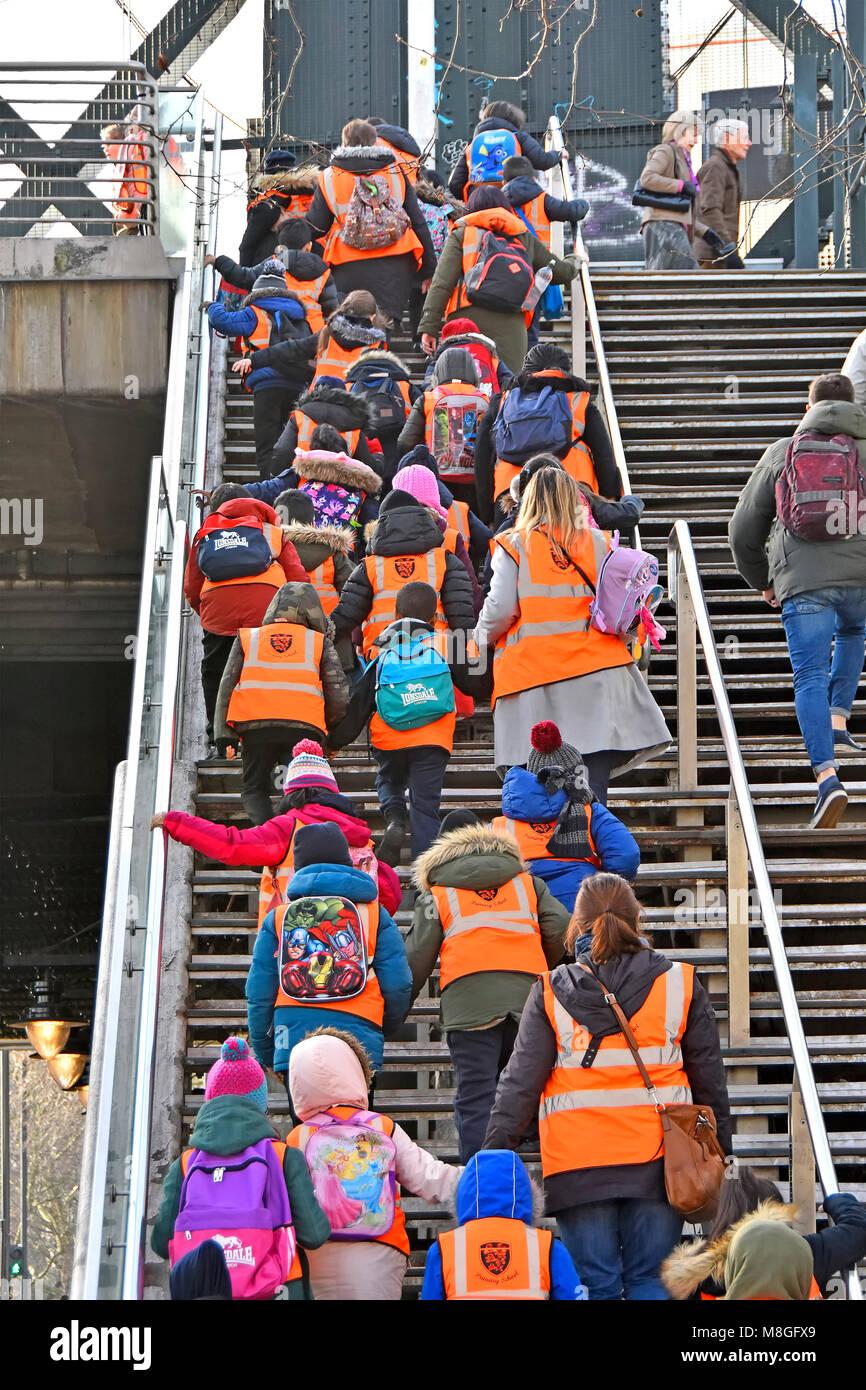 Un grupo de niños de escuela primaria en la escuela de viaje en chaqueta o chaleco de alta visibilidad con Imagen De Stock