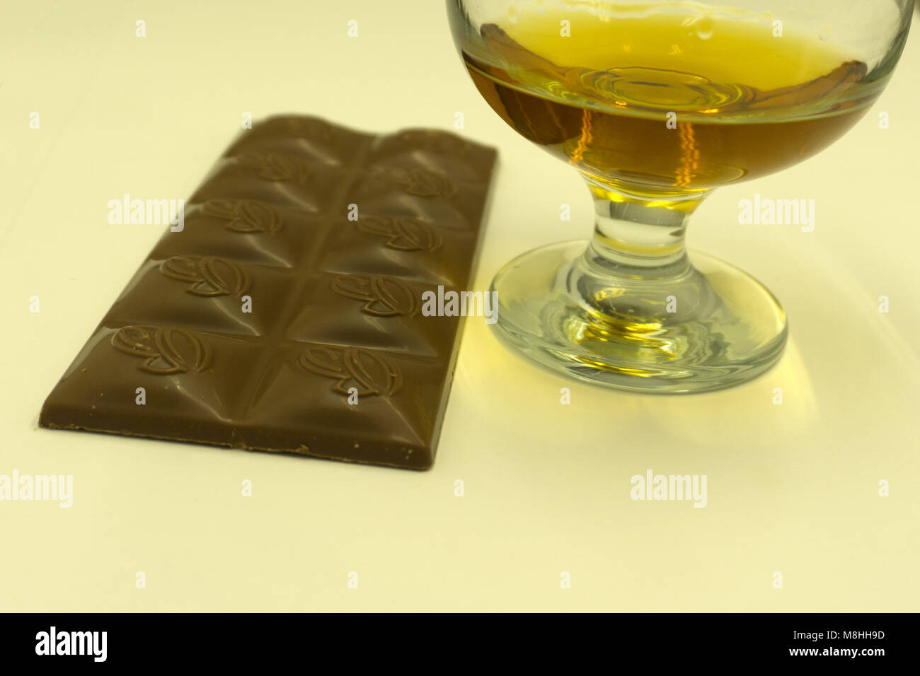 Coñac con barras de chocolate en el fondo de la pila de madera Imagen De Stock