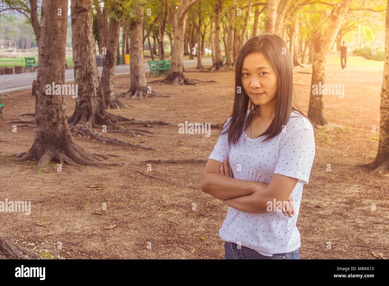 Concepto de vacaciones y días festivos : Mujer vistiendo camiseta blanca. Ella de pie sobre la hierba verde Imagen De Stock