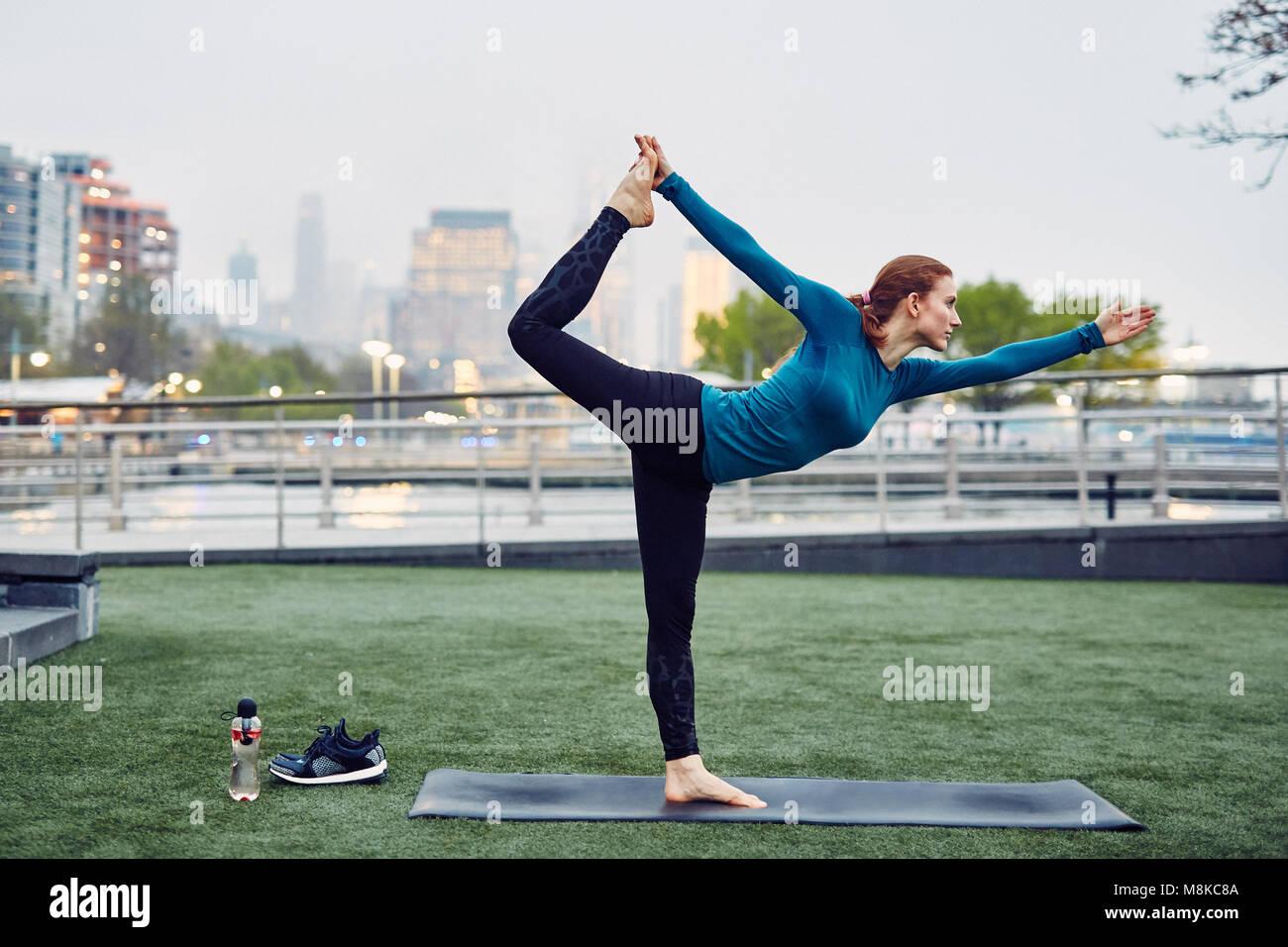 Mujer caucásica realiza yoga en un parque público de la ciudad de Nueva York Imagen De Stock