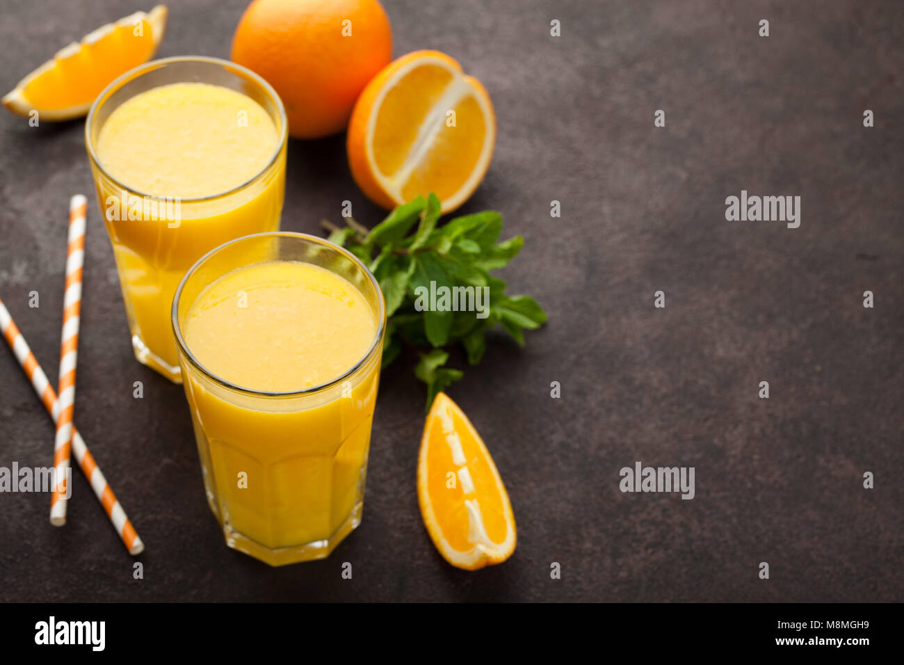 Dos vasos de zumo de naranja recién exprimido y menta sobre un fondo de color marrón oscuro. Vista superior Imagen De Stock